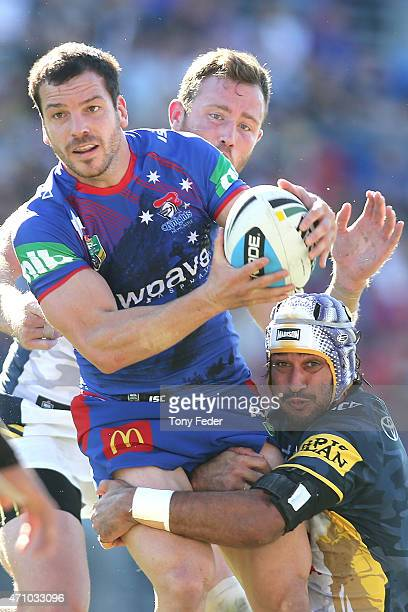 Jarrod Mullen of the Knights is tackled by Johnathan Thurston of the Cowboys during the round eight NRL match between the Newcastle Knights and the...