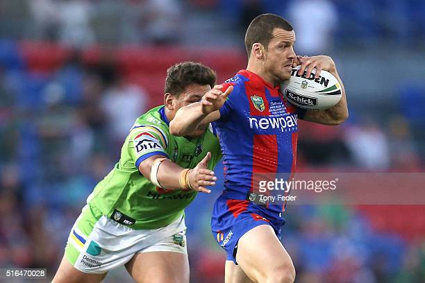 Jarrod Mullen of the Knights is tackled by Josh Papalii of the Raiders during the round three NRL match between the Newcastle Knights and the...