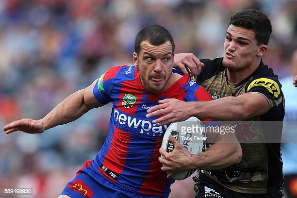 Jarrod Mullen of the Knights is tackled by Nathan Cleary of the Panthers during the round 23 NRL match between the Newcastle Knights and the Penrith...