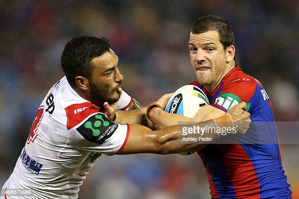 Jarrod Mullen of the Knights is tackled by the Dragons defence during the round five NRL match between the Newcastle Knights and the St George...