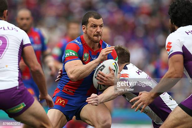 Jarrod Mullen of the Knights is tackled during the round 19 NRL match between the Newcastle Knights and the Melbourne Storm at Hunter Stadium on July...
