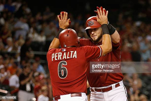 Jarrod Saltalamacchia of the Arizona Diamondbacks highfives David Peralta after hitting a tworun home run against the San Francisco Giants during the...