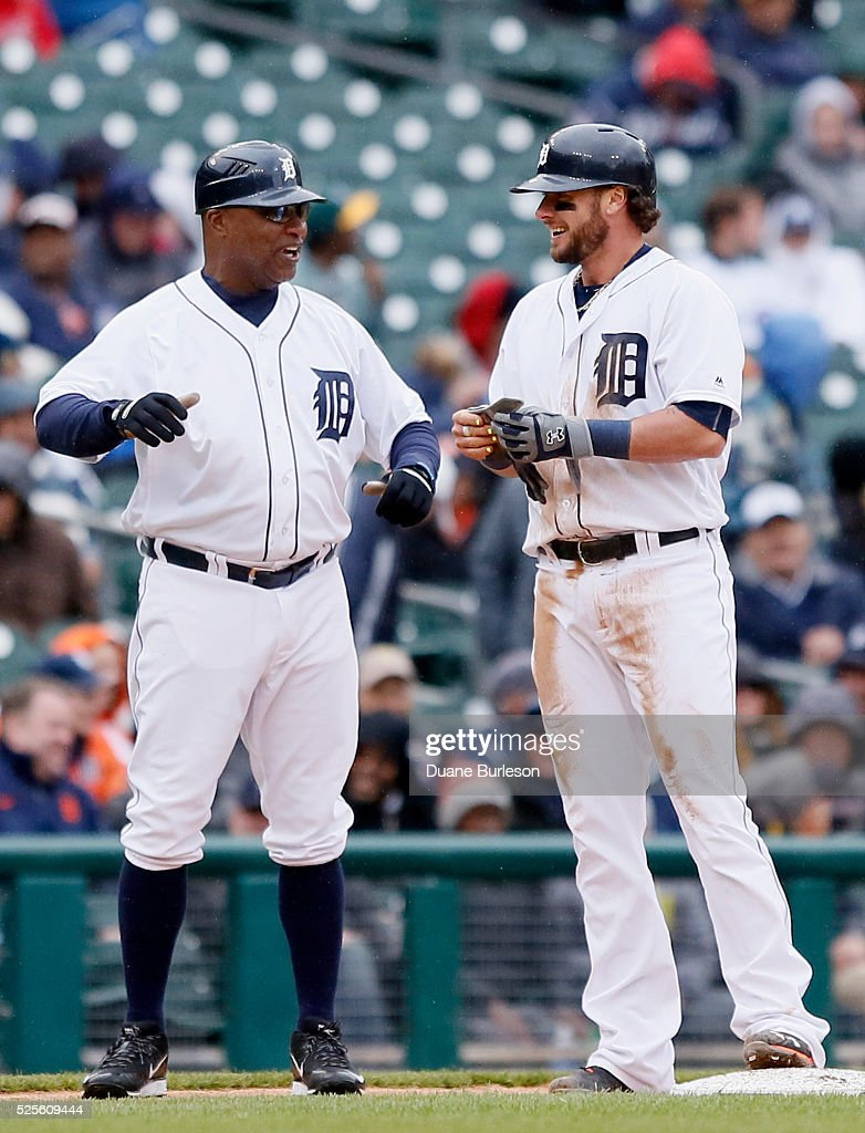 Jarrod Saltalamacchia #39 of the Detroit Tigers smiles with third base coach Dave Clark #25 of the Detroit Tigers after hitting a triple against the Oakland Athletics during the fifth inning at Comerica Park on April 28, 2016 in Detroit, Michigan. The Tigers defeated the Athletics 7-3.