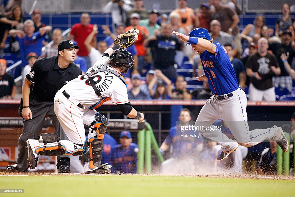 Jarrod Saltalamacchia of the Miami Marlins tags out Kirk Nieuwenhuis of the New York Mets at home plate to stop him from scoring the tying run and...