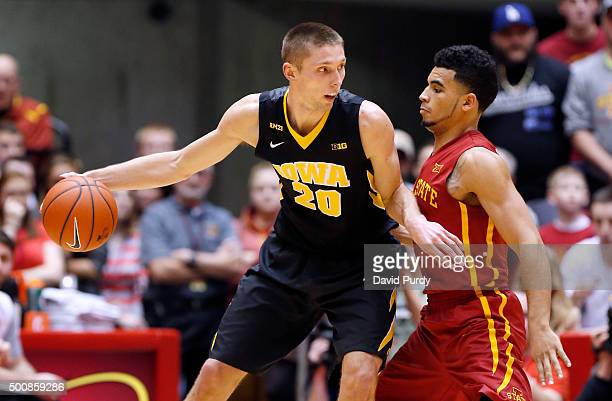 Jarrod Uthoff of the Iowa Hawkeyes drives the ball as Nazareth MitrouLong of the Iowa State Cyclones puts pressure on in the first half of play at...