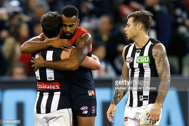 Jarryd Blair of the Magpies and Heritier Lumumba of the Demons embrace as Jamie Elliott of the Magpies looks on during the 2015 AFL round ten match...