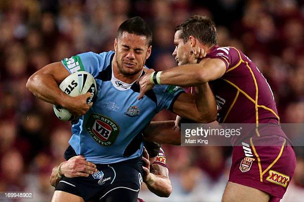 Jarryd Hayne of the Blues is tackled during game one of the ARL State of Origin series between the New South Wales Blues and the Queensland Maroons...
