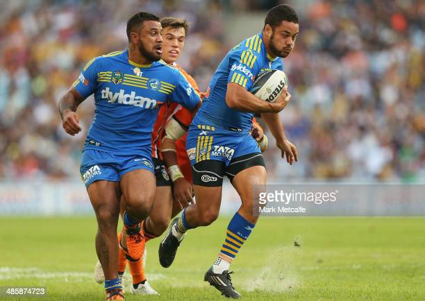 Jarryd Hayne of the Eels breaks through the tackles of Luke Brooks and Sitaleki Akauola of the Tigers to score his second try during the round seven...