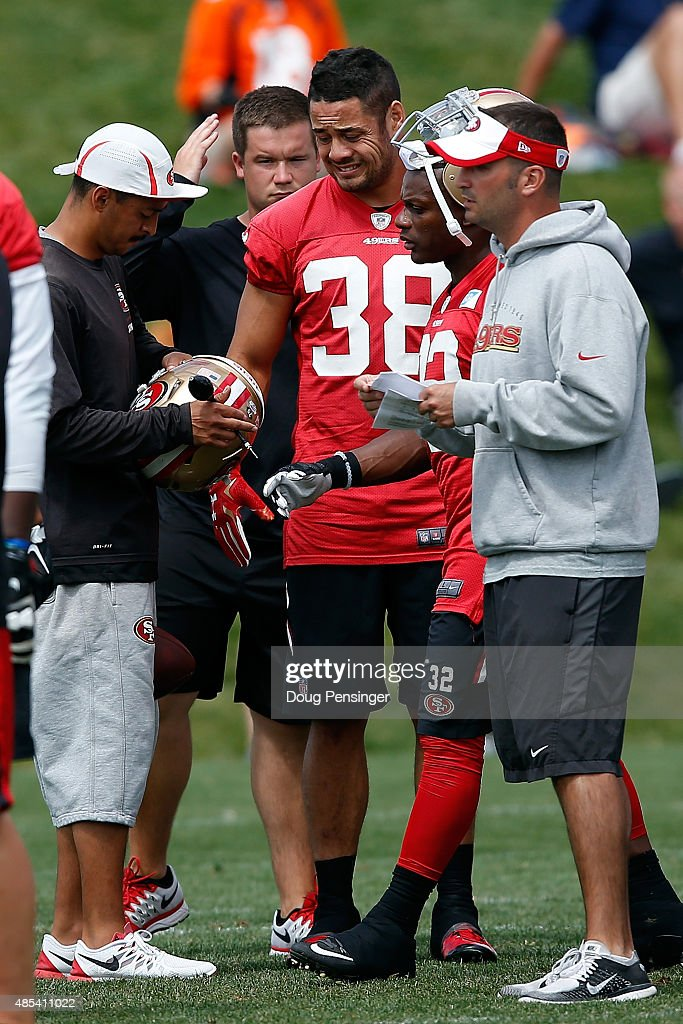 Jarryd Hayne of the San Francisco 49ers has his helmet adjusted as he works out during a joint training session with the San Francisco 49ers and the...