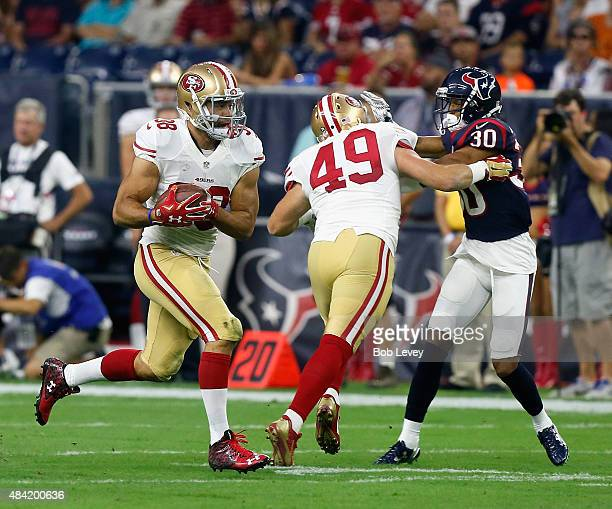 Jarryd Hayne of the San Francisco 49ers rushes with the ball as he gets a block from Bruce Miller on Kevin Johnson of the Houston Texans during a...