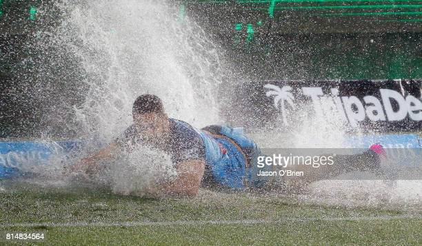 Jarryd Hayne of the Titans hits a puddle of water during the round 19 NRL match between the Gold Coast Titans and the Cronulla Sharks at Cbus Super...