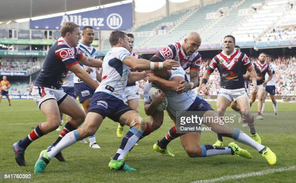 Jarryd Hayne of the Titans is tackled by Blake Ferguson of the Roosters during the round 26 NRL match between the Sydney Roosters and the Gold Coast...