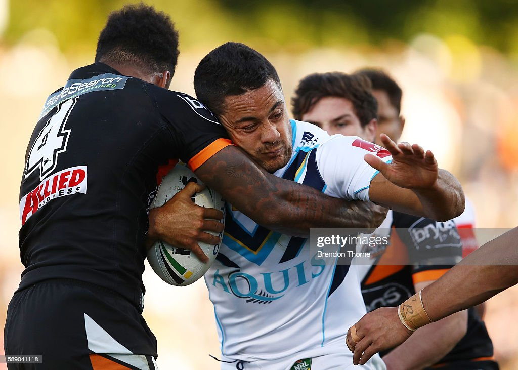 Jarryd Hayne of the Titans is tackled by Kevin Naiqama of the Tigers during the round 23 NRL match between the Wests Tigers and the Gold Coast Titans...