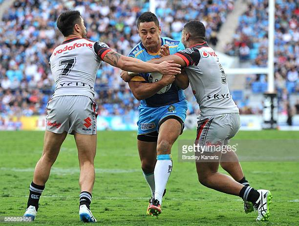 Jarryd Hayne of the Titans takes on the defence in his first run and first match for the club during the round 22 NRL match between the Gold Coast...