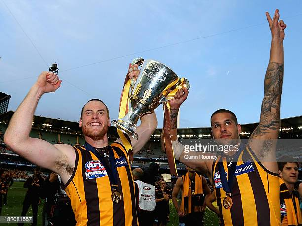 Jarryd Roughead and Lance Franklin of the Hawks celebrates with the Premiership Cup after the hawks won the 2013 AFL Grand Final match between the...