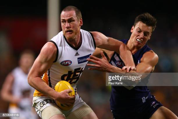 Jarryd Roughead of the Hawks fends off a tackle by Ethan Hughes of the Dockers during the round 18 AFL match between the Fremantle Dockers and the...