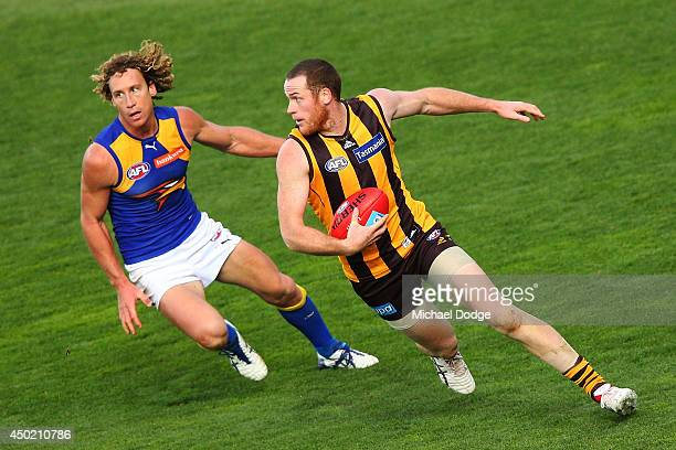 Jarryd Roughead of the Hawks runs with the ball away from Matt Priddis of the Eagles during the round 12 AFL match between the Hawthorn Hawks and the...