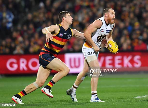 Jarryd Roughead of the Hawks tries to evade a tockle from Josh Jenkins of the Crows during the round 14 AFL match between the Adelaide Crows and the...