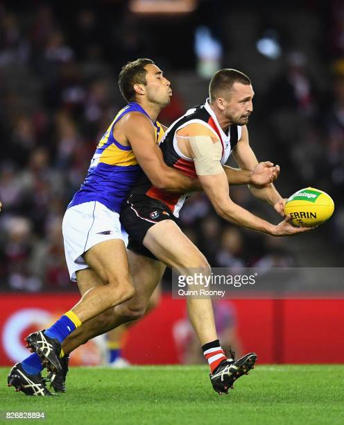 Jarryn Geary of the Saints handballs whilst being tackled by Malcolm Karpany of the Eagles during the round 20 AFL match between the St Kilda Saints...