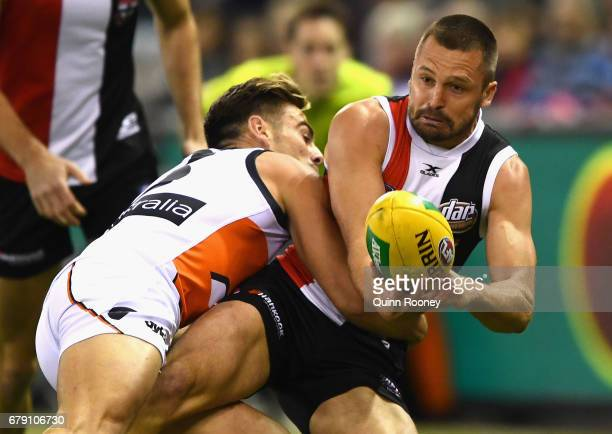 Jarryn Geary of the Saints handballs whilst being tackled by Stephen Coniglio of the Giants during the round seven AFL match between the St Kilda...