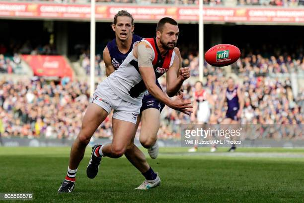 Jarryn Geary of the Saints handpasses the ball under pressure from Nat Fyfe of the Dockers during the round 15 AFL match between the Fremantle...
