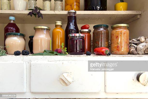 Jars and bottles of home-made food on retro style kitchen cabinet