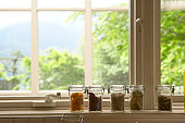Jars containing dried fruits and vegetables on window sill