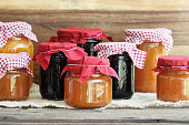 Variety of homemade jams and preserves covered with checkered and red cloth against a rustic background. Extreme shallow depth of field with selective focus on jar in front. Assortment includes peach