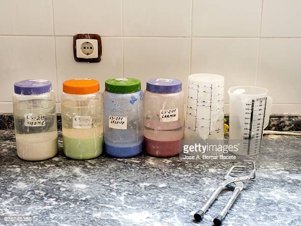 Jars of painting for ceramics on a desk with tools