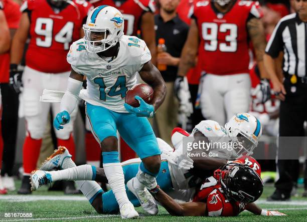 Jarvis Landry of the Miami Dolphins attempts to break a tackle by Brian Poole of the Atlanta Falcons at MercedesBenz Stadium on October 15 2017 in...