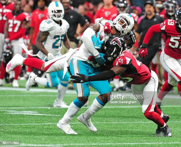 Jarvis Landry of the Miami Dolphins is tackled by Deion Jones and Ricardo Allen of the Atlanta Falcons at MercedesBenz Stadium on October 15 2017 in...