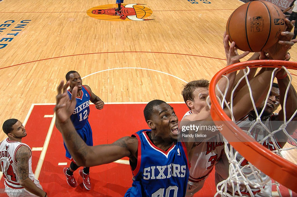 Jarvis Varnado of the Philadelphia 76ers grabs a rebound against Mike Dunleavy and Jimmy Butler of the Chicago Bulls on March 22 2013 at the United...
