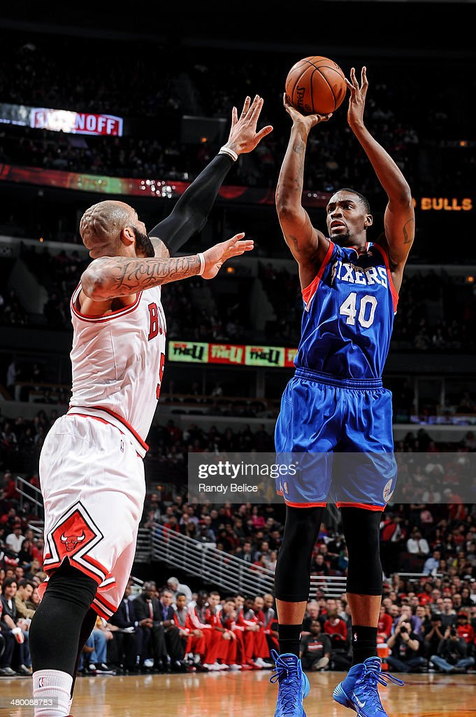 Jarvis Varnado of the Philadelphia 76ers shoots against Carlos Boozer of the Chicago Bulls on March 22 2013 at the United Center in Chicago Illinois...