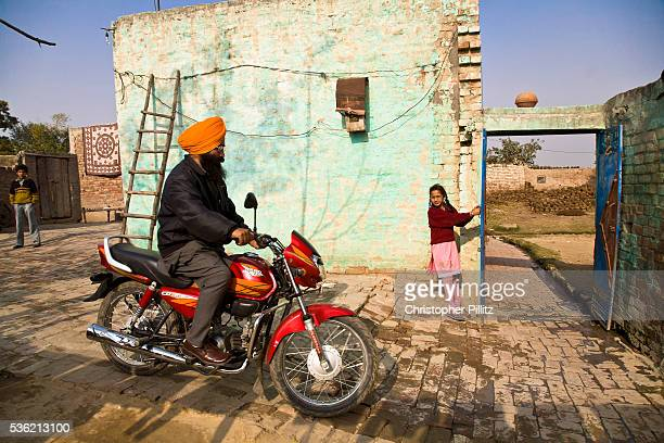 Jasbir Kaur opens the gate of the family home to allow her father to head to work Chita Kalaan village Punjab India | Location Chita Kalaan Village...