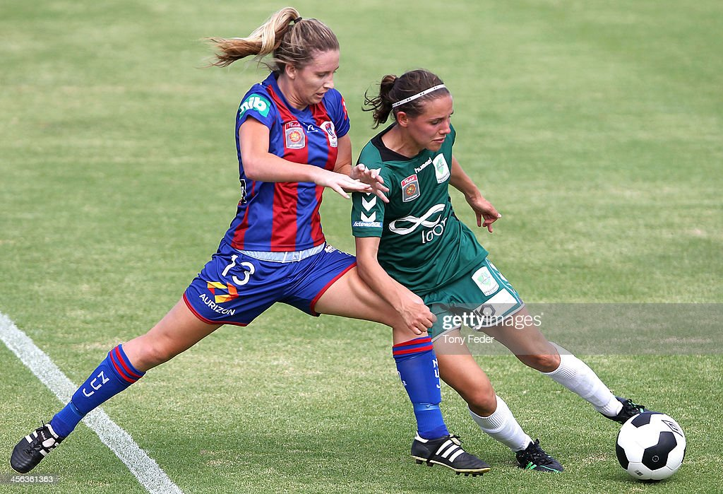 Jasmin Courtenay of the Jets attacks Nicole Sykes of Canberra United during the round five W-League match between the Newcastle Jets and Canberra United at Wanderers Oval on December 14, 2013 in Newcastle, Australia.