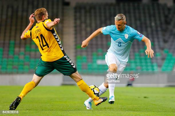 Jasmin Kurtic of Slovenia competes with Vykintas Slivka of Lithuania during the FIFA 2018 World Cup Qualifier between Slovenia and Lithuania at...