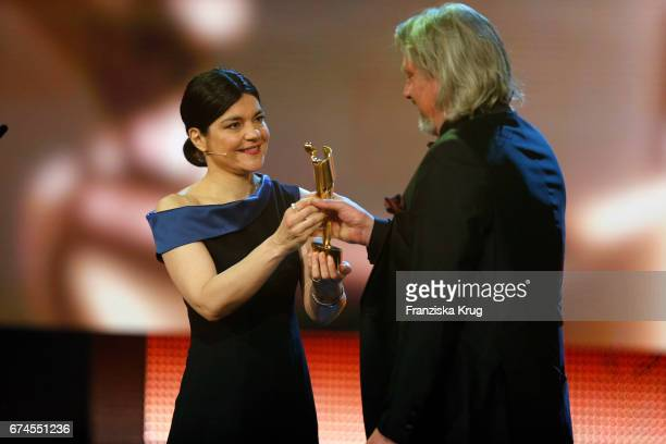 Jasmin Tabatabai host of the Awards on stage shaking hands with Tim Pannen who receives the Award for Best Production Design at the Lola German Film...