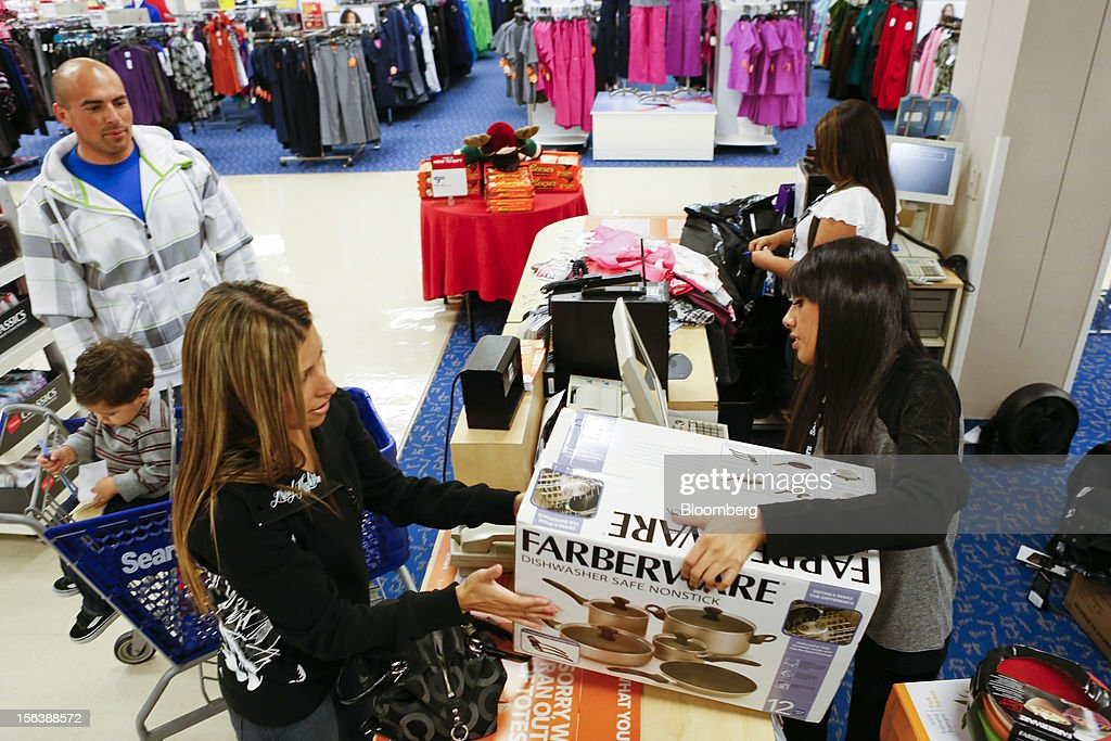 Jasmine Burich purchases a Farberware cookware set on sale at the Sears store during the Family and Friends evening sale inside the Del Amo shopping mall in Torrance, California, U.S., on Sunday, Nov. 11, 2012. Sears Holdings Corp. is scheduled to announce earnings results on Nov. 15 before the opening of U.S. financial markets. Photographer: Patrick Fallon/Bloomberg via Getty Images