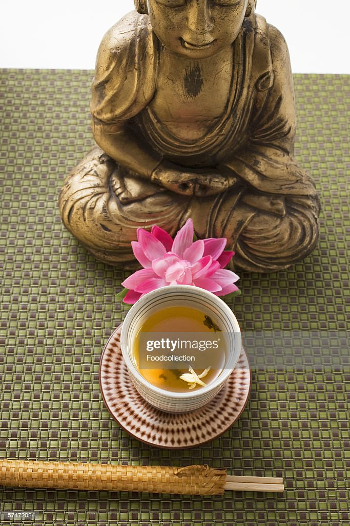 Jasmine tea in small bowl in front of Buddha : Stock Photo