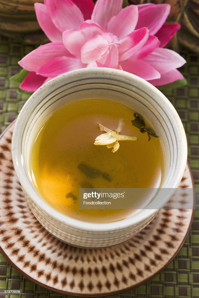Jasmine tea in small bowl in front of water lily : Stock Photo