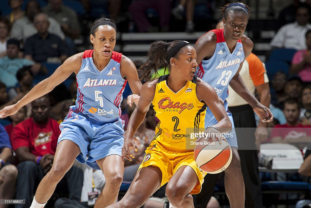 Jasmine Thomas #5 and Aneika Henry #13 of the Atlanta Dream defend against Candice Wiggins #2 of the Tulsa Shock during the WNBA game on July 21, 2013 at the BOK Center in Tulsa, Oklahoma.