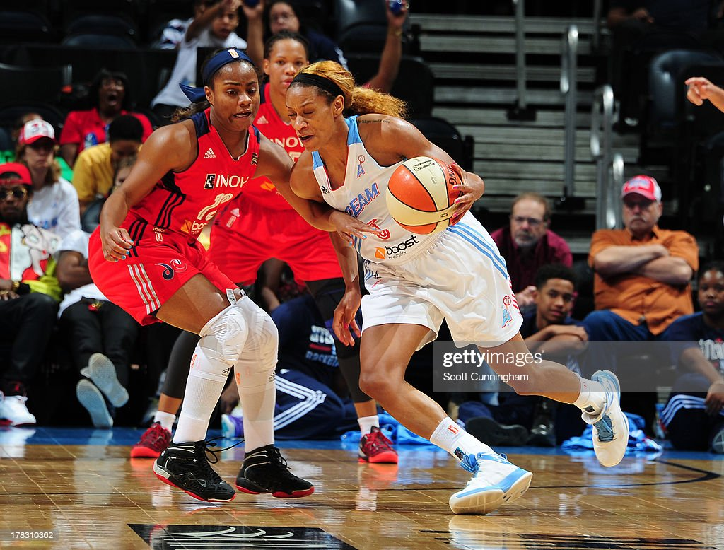 Jasmine Thomas #5 of the Atlanta Dream drives against Ivory Latta #12 of the Washington Mystics at Philips Arena on August 28 2013 in Atlanta, Georgia.