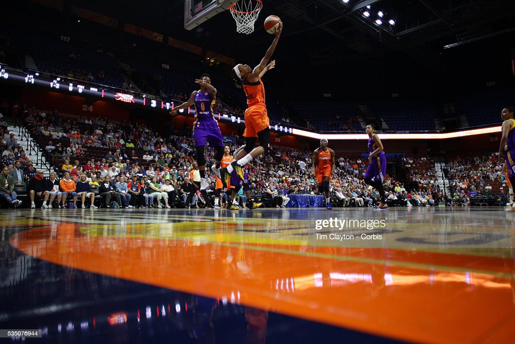 Jasmine Thomas #5 of the Connecticut Sun scores two points with a reverse layup while defended by Alana Beard #0 of the Los Angeles Sparks during the Los Angeles Sparks Vs Connecticut Sun, WNBA regular season game at Mohegan Sun Arena on May 26, 2016 in Uncasville, Connecticut.