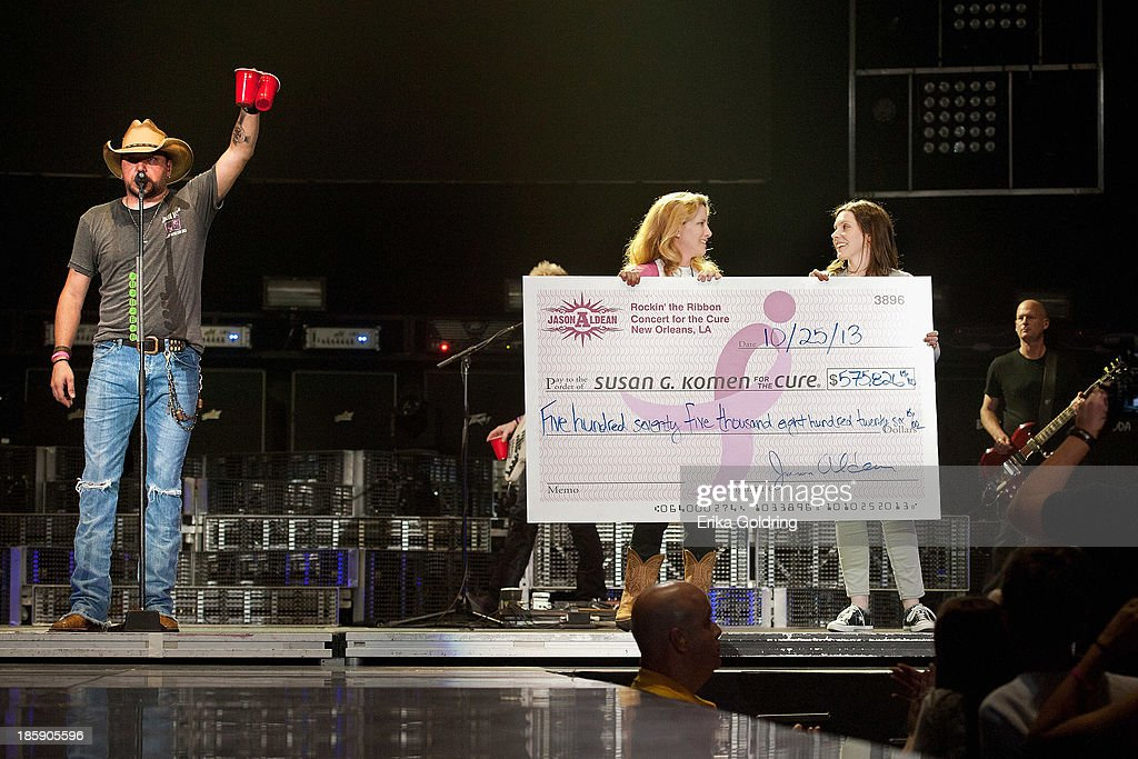 Jason Aldean (L) and Stephanie Alderman (R) present executive Director of Susan G. Komen for the Cure New Orleans Lisa Westbrook Plunkett (C) with a check for $575,826.15 during the 8th annual Susan G. Komen Concert for the Cure at New Orleans Arena on October 25, 2013 in New Orleans, Louisiana.