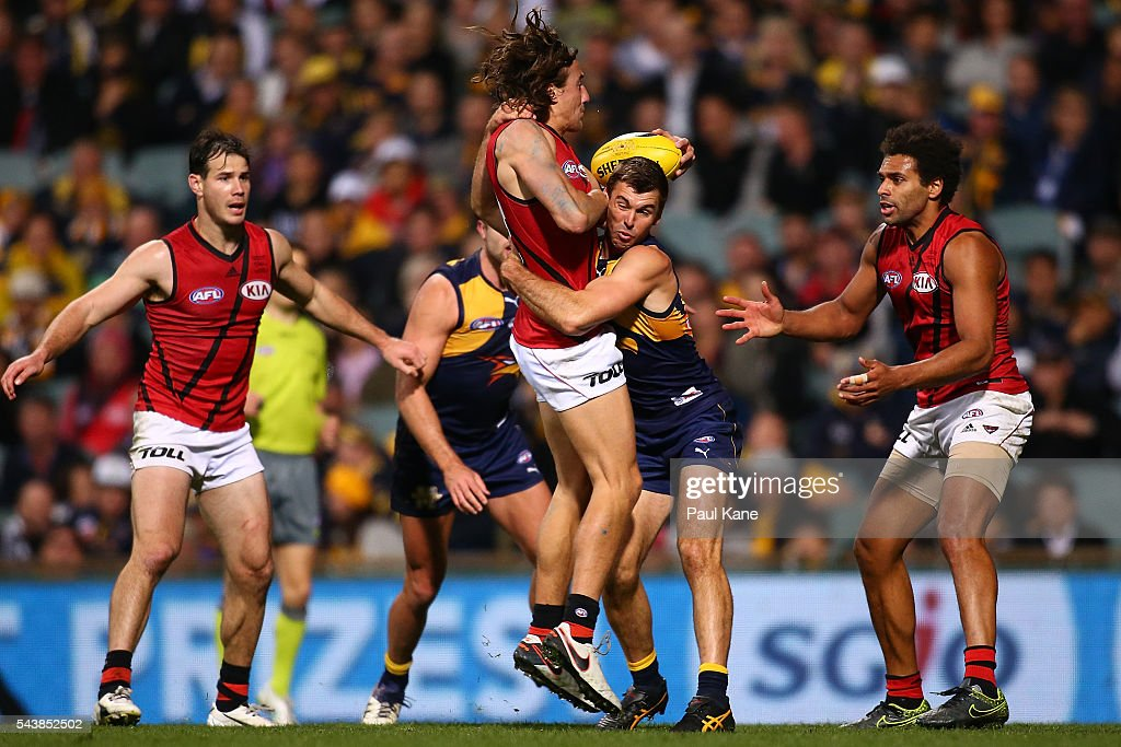 Jason Ashby of the Bombers gets tackled by Jamie Cripps of the Eagles during the round 15 AFL match between the West Coast Eagles and the Essendon Bombers at Domain Stadium on June 30, 2016 in Perth, Australia.