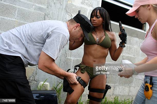 Jason Atkins creator/producer helps Mia Lawrence with a holster as she prepares to film a scene on the set of Girls and Guns a webbased reality show...