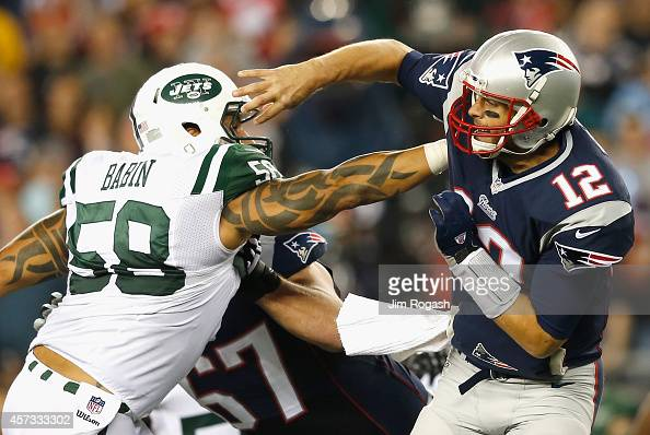 Jason Babin of the New York Jets tackles Tom Brady of the New England Patriots during the second quarter at Gillette Stadium on October 16 2014 in...