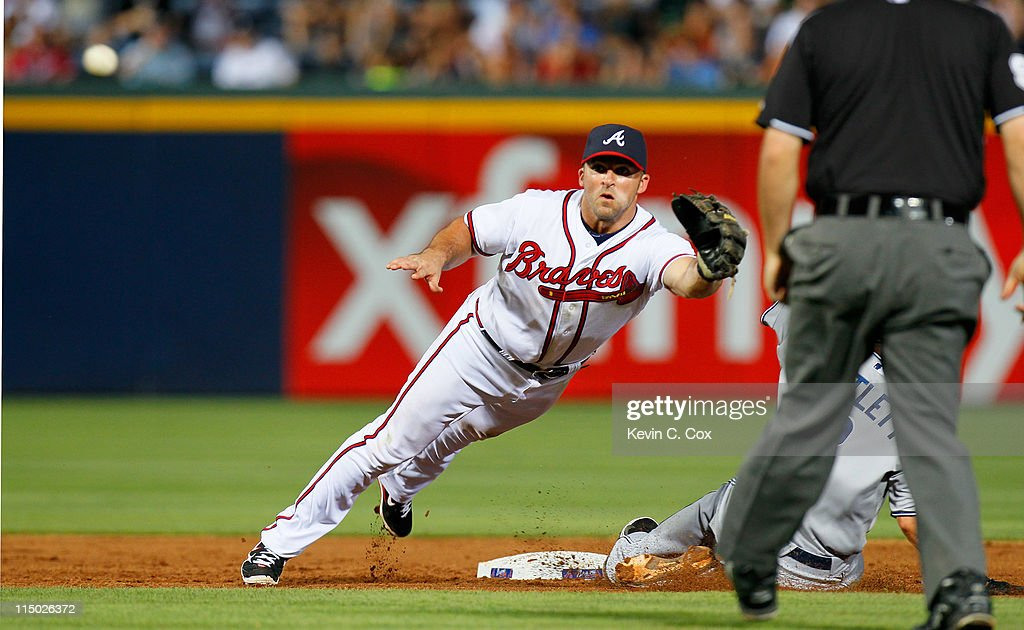 Jason Bartlett #8 of the San Diego Padres steals second base under a bad throw to <a gi-track='captionPersonalityLinkClicked' href=/galleries/search?phrase=Dan+Uggla&family=editorial&specificpeople=542208 ng-click='$event.stopPropagation()'>Dan Uggla</a> #26 of the Atlanta Braves at Turner Field on June 1, 2011 in Atlanta, Georgia.