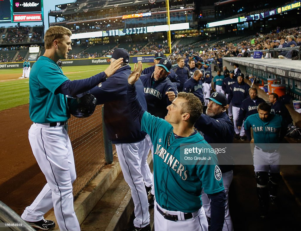 <a gi-track='captionPersonalityLinkClicked' href=/galleries/search?phrase=Jason+Bay&family=editorial&specificpeople=214251 ng-click='$event.stopPropagation()'>Jason Bay</a> #12 (L) of the Seattle Mariners is congratulated by <a gi-track='captionPersonalityLinkClicked' href=/galleries/search?phrase=Brendan+Ryan&family=editorial&specificpeople=835643 ng-click='$event.stopPropagation()'>Brendan Ryan</a> #26 after scoring on an RBI single by Raul Ibanez in the first inning against the Texas Rangers at Safeco Field on April 12, 2013 in Seattle, Washington.