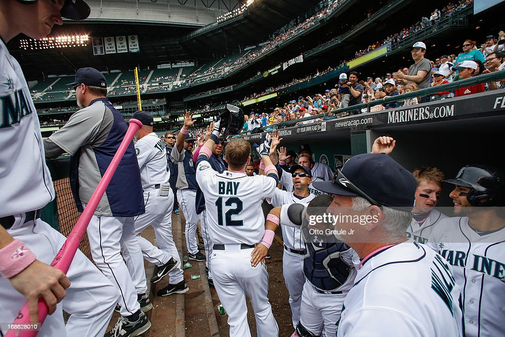 <a gi-track='captionPersonalityLinkClicked' href=/galleries/search?phrase=Jason+Bay&family=editorial&specificpeople=214251 ng-click='$event.stopPropagation()'>Jason Bay</a> #12 of the Seattle Mariners is congratulated by teammates after hitting a home run in the seventh inning against the Oakland Athletics at Safeco Field on May 12, 2013 in Seattle, Washington.